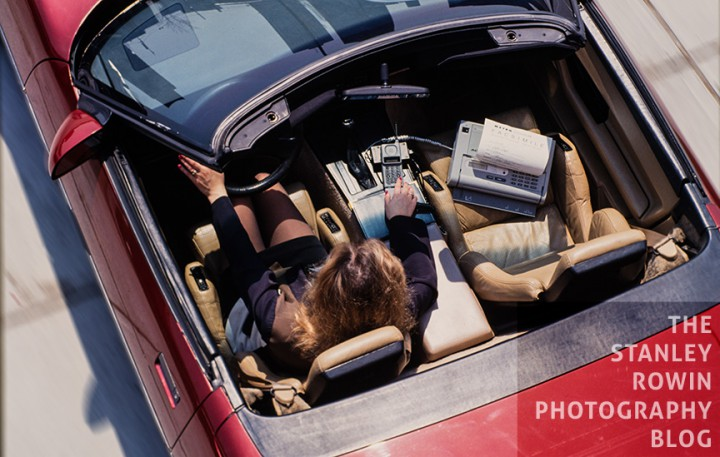 Aerial view of convertable car with woman driver faxing via cell phone